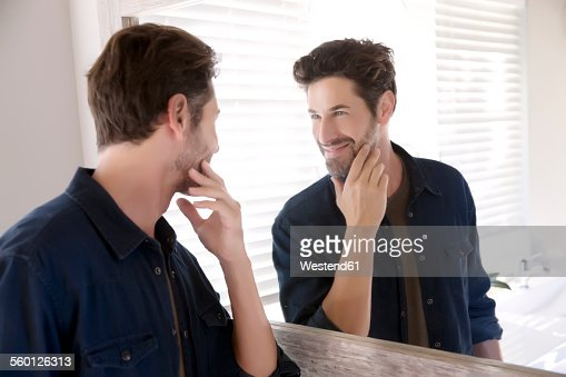 Man watching himself at bathroom mirror