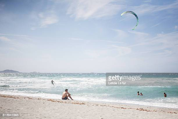 Man watching kite surfers and swimmers on a beach in Corsica France