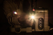 Man in white shirt, in dark interior, watching movie on vintage russian 8mm projector and adjusting lense - front view with light flare.