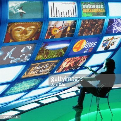 Man watching multiple television screens (Digital Composite) : Stock Photo