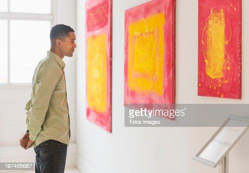 Man watching paintings in modern art gallery : Stock Photo