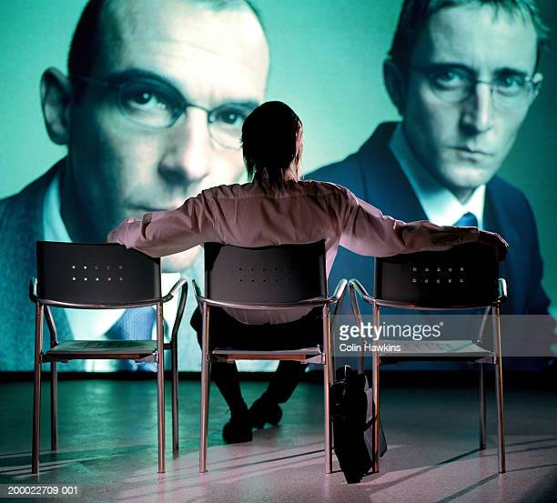 Man watching projection of two businessmen, rear view