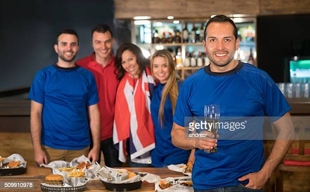 Man watching sports with friends at a bar