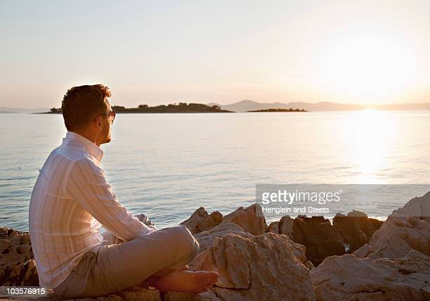 Man watching sun set at rocky beach