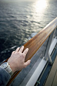 Man watching sunrise from cruise ship, close-up of hand on railing
