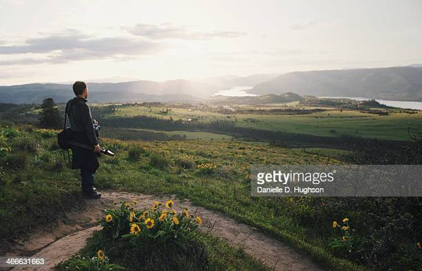 Man Watching Sunset Over Field of Wildflowers
