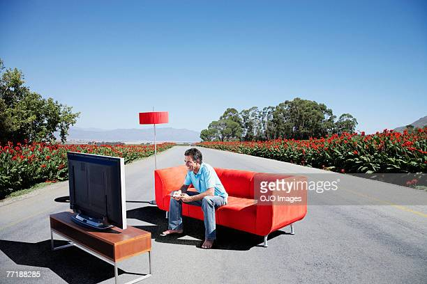A man watching television on a couch in the road