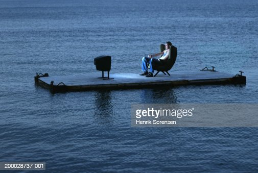 Man watching television on raft at sea