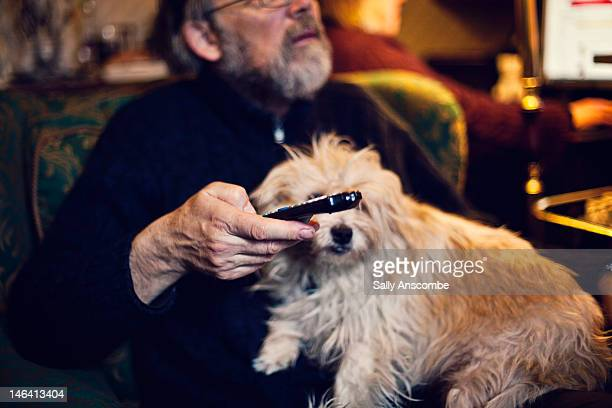 Man watching television with his dog