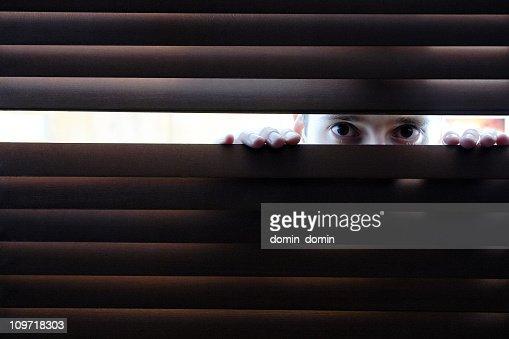 Man watching through blinds : Stock Photo