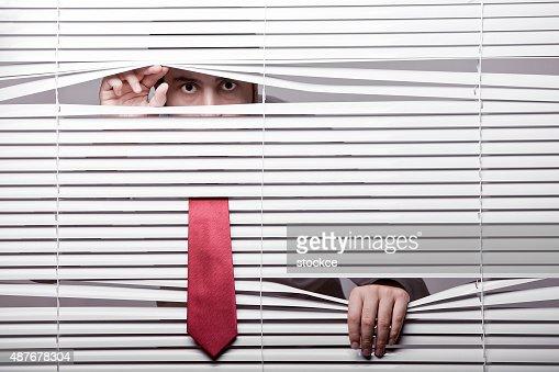 Man Watching through window blinds : Stock Photo