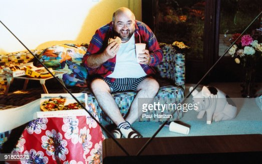 Man watching tv and eating junk food : Stock Photo