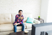 Hispanic attractive man using remote control while spending weekend at home