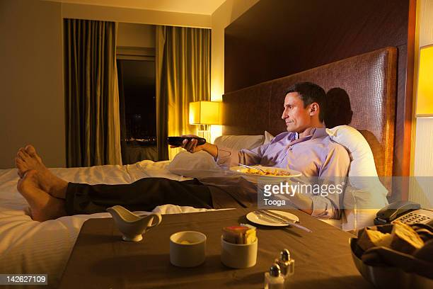 Man watching tv in hotel eating room service