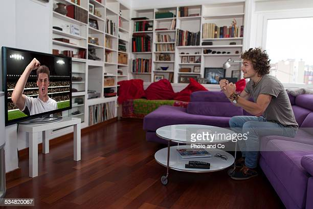 man watching tv indoors exulting