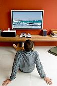 Man watching TV sitting on floor