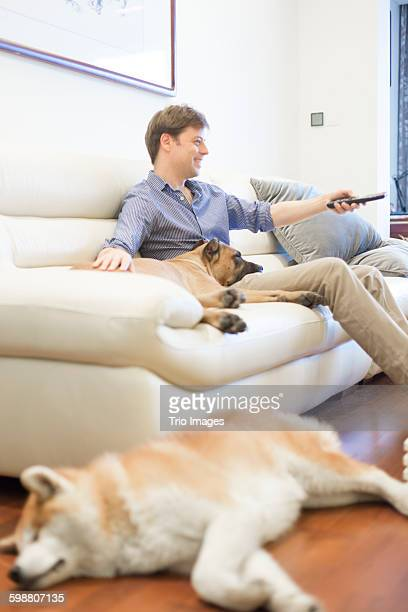 man watching TV with pet dog at home