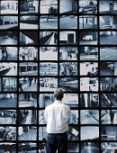 Man watching wall of surveillance screens