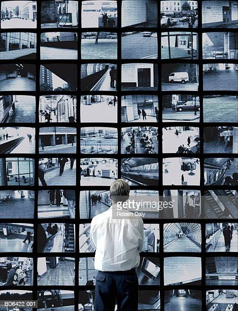 Man watching wall of surveillance screens