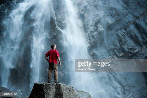 Man watching waterfall : Stock Photo