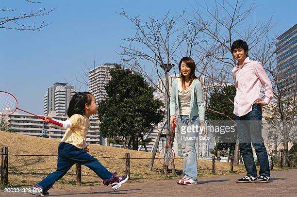 Man watching woman and daughter (3-5) play racquet