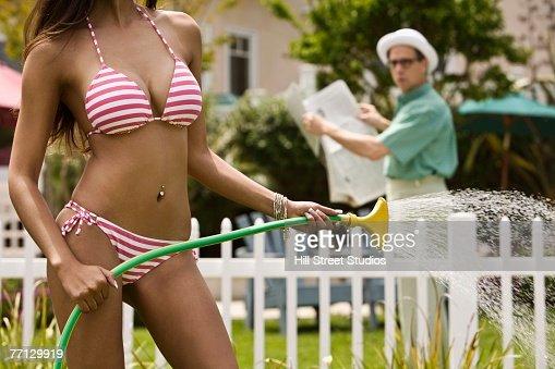 Man watching woman in bikini water plants