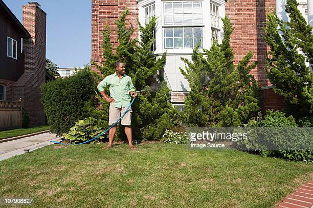 Man watering grass with hosepipe