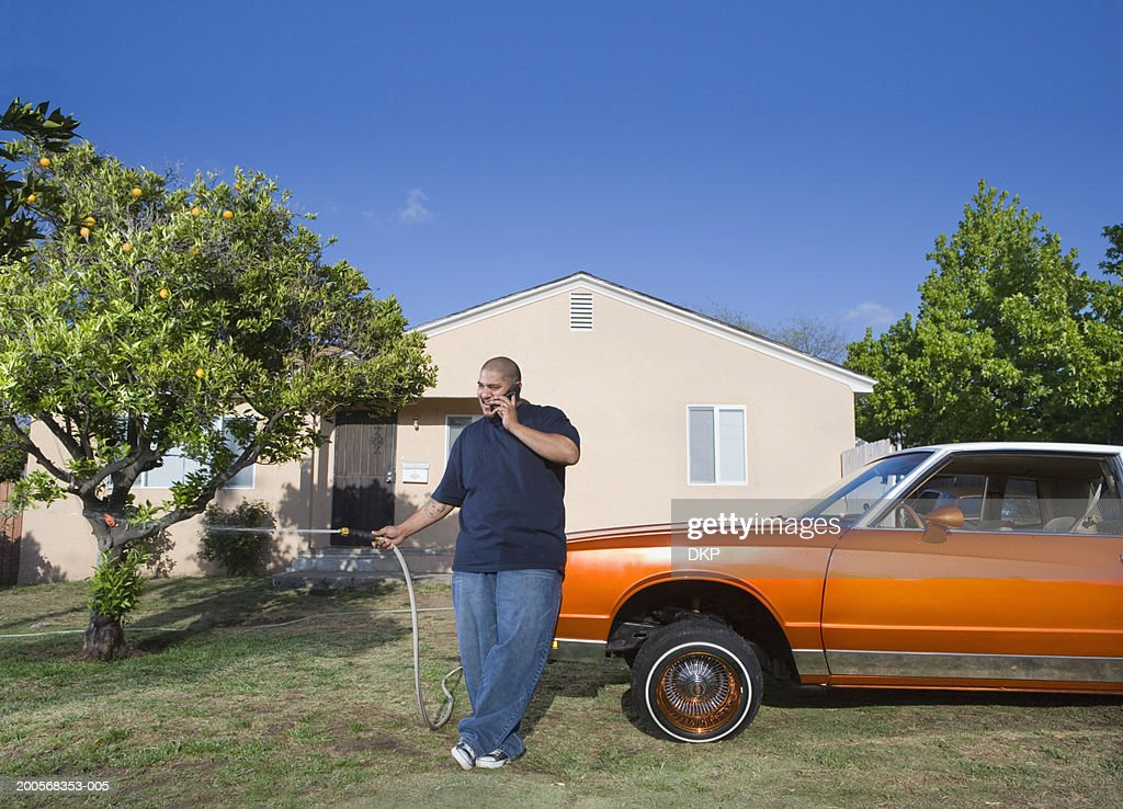 Man watering lawn and talking on cellular phone : Stock Photo