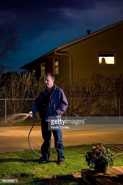 Man watering lawn at night, neighbor watching