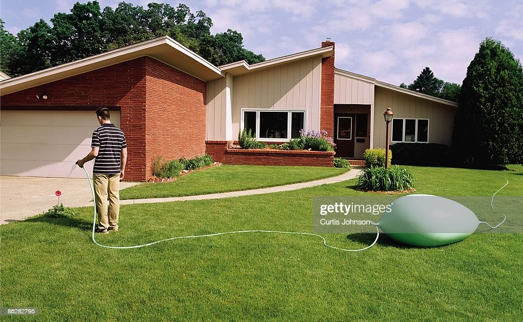 Man watering yard with kinked garden hose