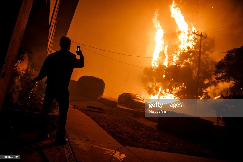 A man waters the front of a building and takes a picture of a flame getting closer to homes on December 5, 2017 in Ventura, California.
