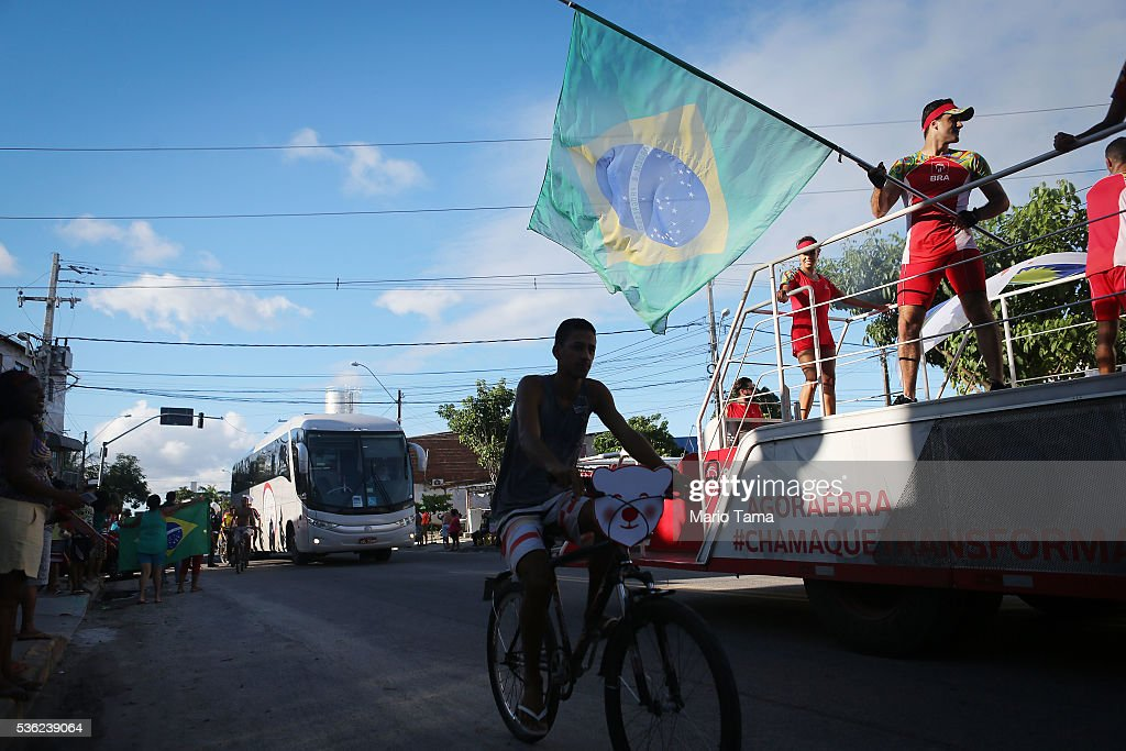 A man waves a Brazilian flag along the Olympic torch route ahead of the torchbearer on May 31, 2016 in Recife, Brazil. The Olympic flame will pass through 329 cities from all states from the north to the south of Brazil, before arriving in Rio de Janeiro on August 5, for the lighting of the cauldron for the Rio 2016 Olympic Games. The games will be held amidst an economic and political crisis in the country.