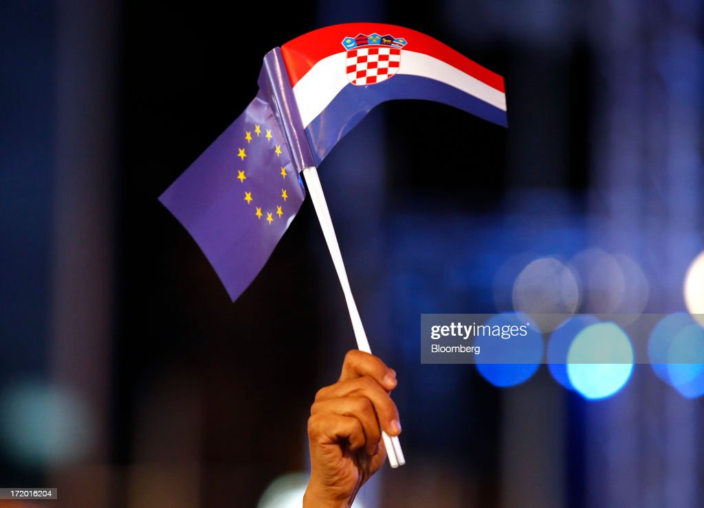 A man waves a Croatian national flag, right, and European Union (EU) flag during celebrations in Ban Jelacic square as Croatia marks it's entry into the European Union (EU) in Zagreb, Croatia, on Sunday, June 30, 2013. Croatia will become the European Union's 28th member at midnight, the bloc's first addition since Bulgaria and Romania joined in 2007. Photographer: Simon Dawson/Bloomberg via Getty Images