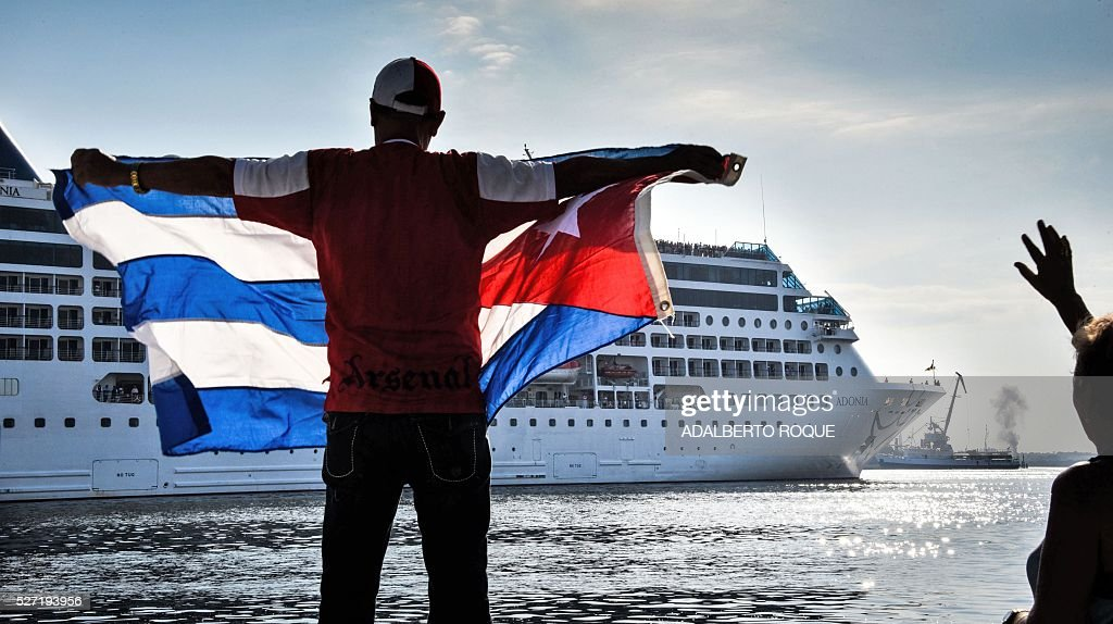 A man waves a Cuban flag at the Malecon waterfront as the first US-to-Cuba cruise ship to arrive in the island nation in decades glides into the port of Havana, on May 2, 2016. The first US cruise ship bound for Cuba in half a century, the Adonia -- a vessel from the Carnival cruise's Fathom line -- set sail from Florida on Sunday, marking a new milestone in the rapprochement between Washington and Havana. The ship -- with 700 passengers aboard -- departed from Miami, the heart of the Cuban diaspora in the United States. / AFP / ADALBERTO