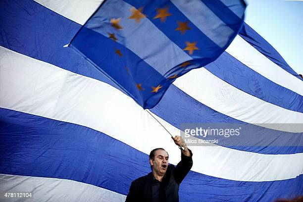 A man waves a EU flag as proEuro protesters take part in a rally in front of the Parliament on June 22 2015 in Athens Greece Thousends of people...