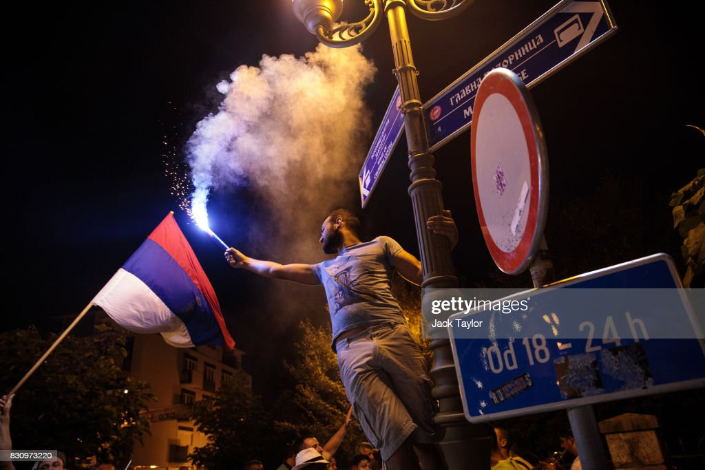 A man waves a flare as he hangs from a lamp post in the town centre during the Guca Trumpet Festival on August 11, 2017 in Guca, Serbia. Thousands of revellers attend the trumpet festival, held annually since 1961 in the small, central Serbian town of Guca. The free event is a celebration of Balkan music with dozens of orchestras and solo trumpeters taking part in the festival's main competition. During the festival wild street parties take place throughout the night as brass bands parade and play for tips to the thousands of visitors in the town's restaurants, bars and pop-up tents.
