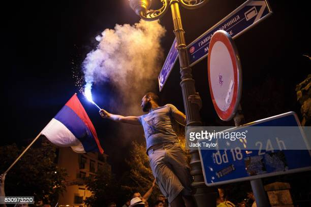 A man waves a flare as he hangs from a lamp post in the town centre during the Guca Trumpet Festival on August 11 2017 in Guca Serbia Thousands of...
