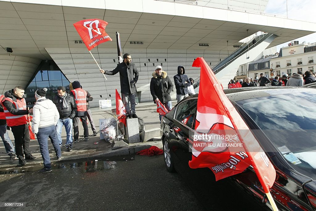 A man waves a Force Ouvriere (FO) trqde union flag as drivers of Uber and other ride-hailing companies, known in France as 'voitures de tourisme avec chauffeur' (VTC), a class of companies that allow passengers to book rides with independent professional chauffeurs, gather at Porte Maillot in Paris on February 11, 2016, to defend jobs they believe are threatened by measures the government recently announced in favor of taxis. / AFP / MATTHIEU ALEXANDRE
