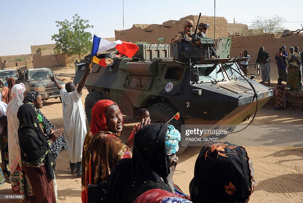 A man (L) waves a French and a Malian national flags while locals welcome French soldiers in Bourem northen Mali on February 17, 2013. Leaders in Africa's Sahel region called on Saturday for further efforts to support Mali as they announced new funds to back a West African force in the country. A French-led military intervention launched on January 11 has driven the Islamist rebels in Mali from the towns they controlled, but concerns remain over stability amid suicide attacks and guerrilla fighting. GUYOT