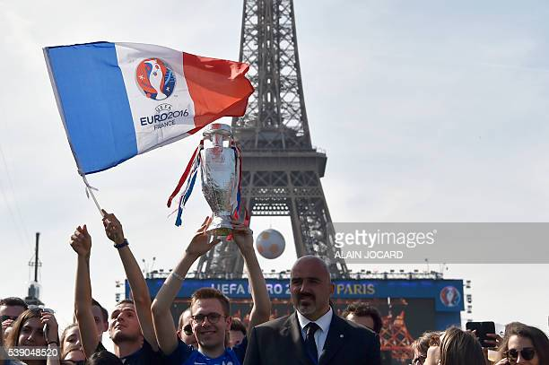 A man waves a French flag with the Euro 2016 logo as people gather in the fan zone behind the Eiffel Tower on the Champs de Mars during the opening...