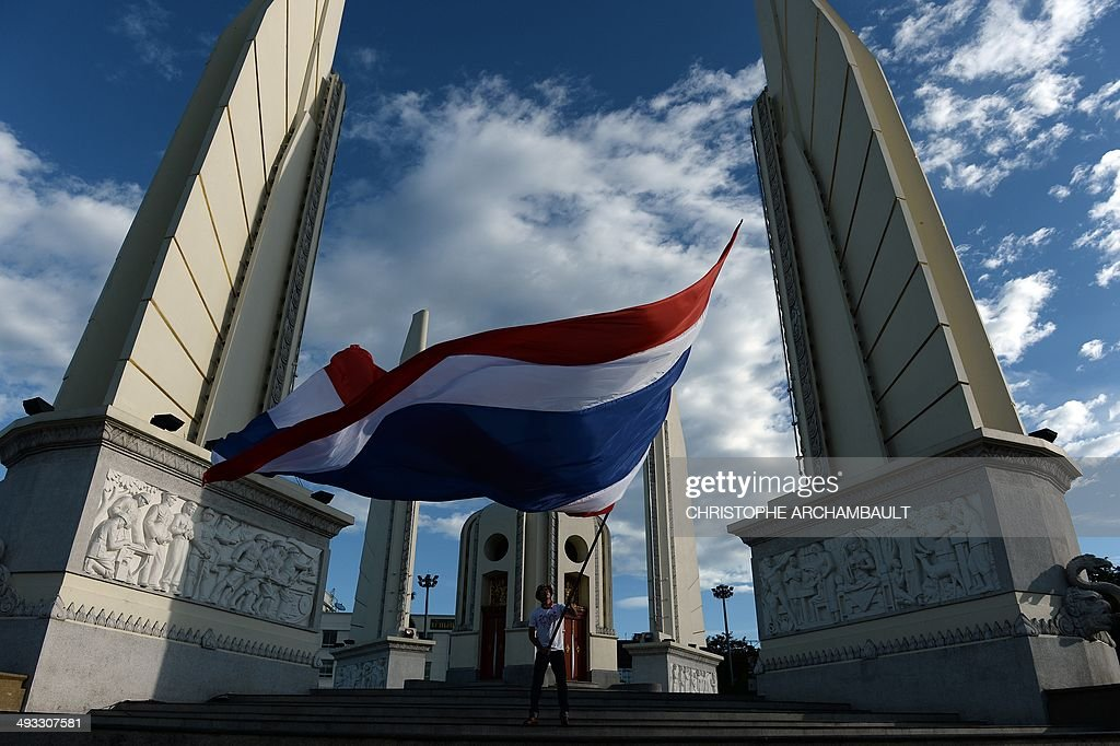 A man waves a giant national flag at Democracy Monument as the site of months of antigovernment protests is cleaned up a day after the Thai army...