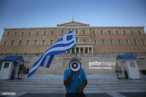 A man waves a Greek flag and uses a megaphone in front of the Greek parlaiment during a proeuropean rally on July 9 2015 in Athens Greece The Greek...