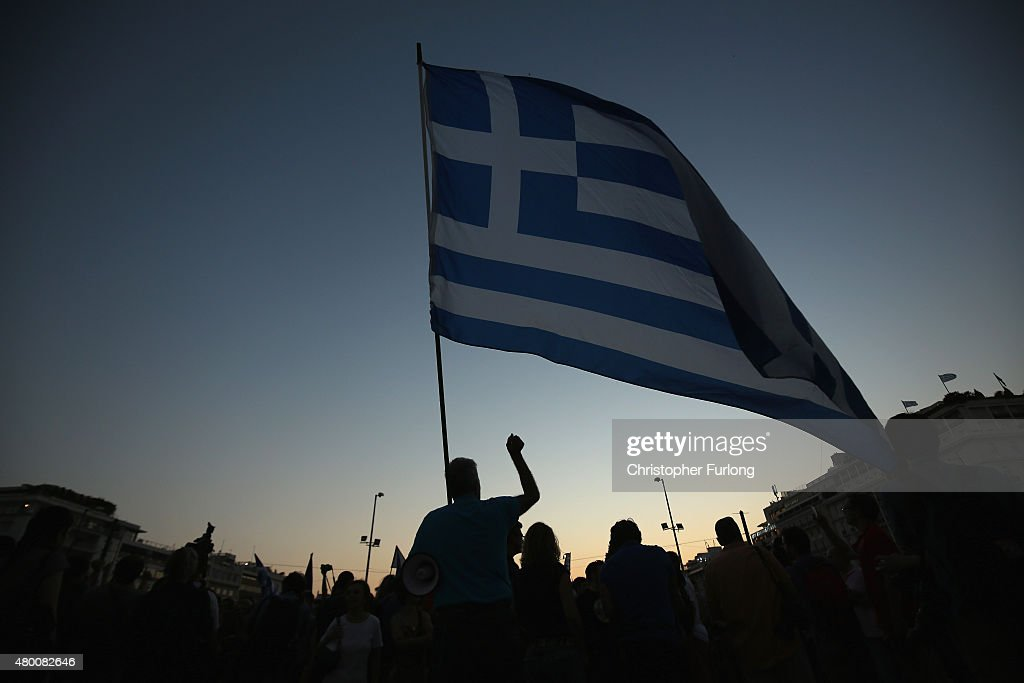 A man waves a Greek flag in front of the Greek parlaiment during a proeuropean rally on July 9 2015 in Athens Greece The Greek government has only...