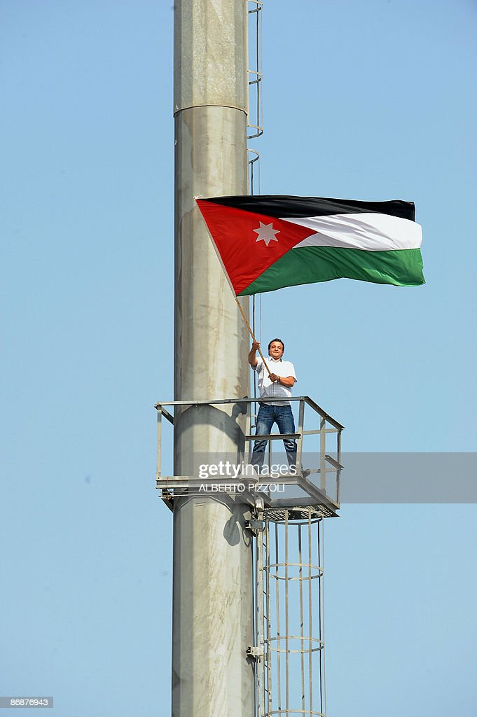 A man waves a Jordanian flag as Pope Benedict XVI celebrates mass at Amman's football stadium on May 10, 2009. The pontiff urged Christians at the open-air mass to be faithful to their roots in the troubled Middle East where decades of conflict have forced many to emigrate.
