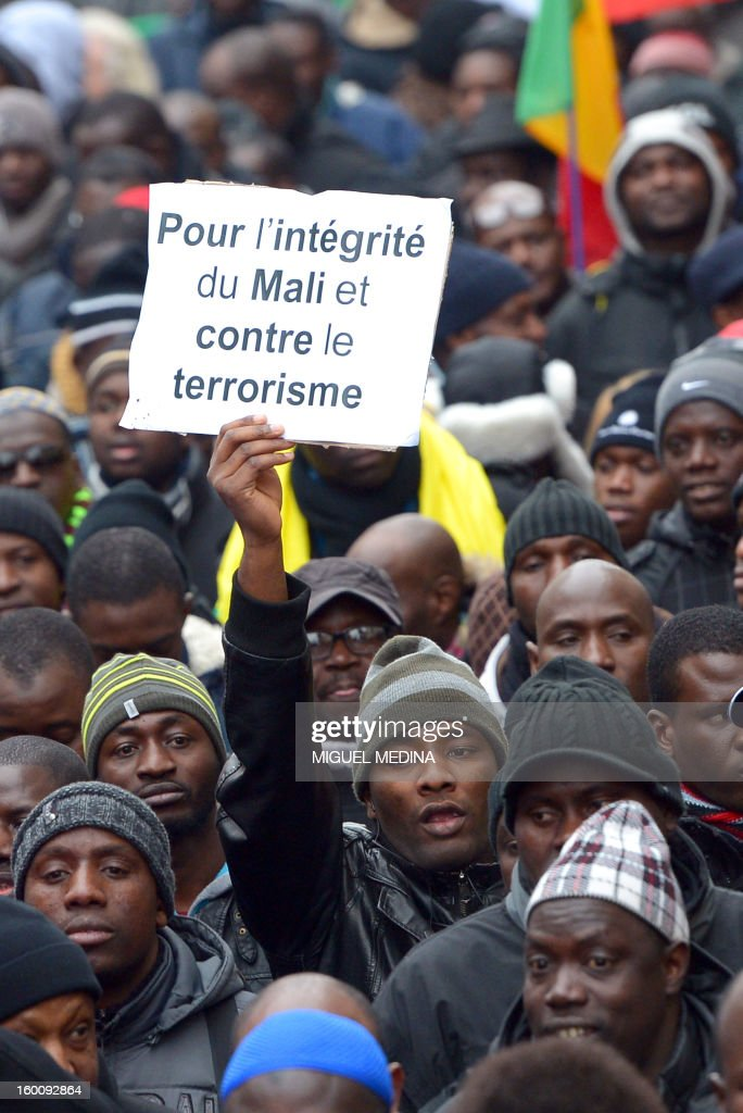 A man waves a placard during a demonstration, organized by Malian associations, in support of the liberation forces of Mali on January 26, 2013 in Montreuil, near Paris. Placard reads 'For a united Mali, against terrorism'.