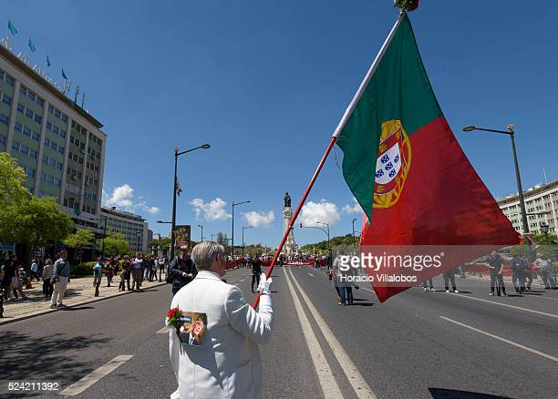 A man waves a Portuguese flag before participating in the parade to celebrate the 42nd Anniversary of The Carnation Revolution on April 25 2016 in...