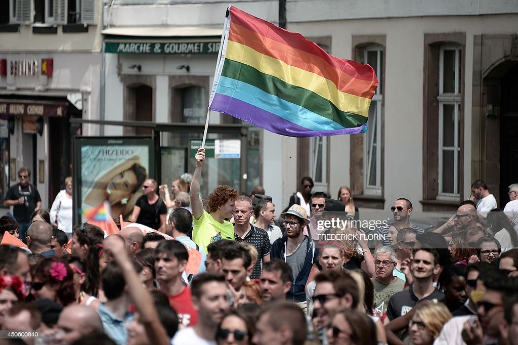 A man waves a Rainbow flag as people take part in the 13th annual local edition of the Gay Pride homosexual, bisexual and transgender visibility march on June 14, 2014, in Strasbourg, eastern France. Drag queens, civil rights activists and scantily clad gay and straight couples made their way through the city to the thumping of dance music.