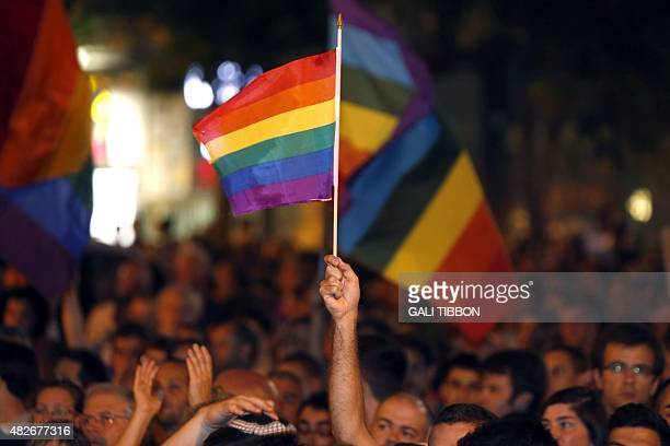 A man waves a rainbow flag as thousands of Israelis from the gay community and supporters gather in downtown Jerusalem on August 1 2015 to protest...