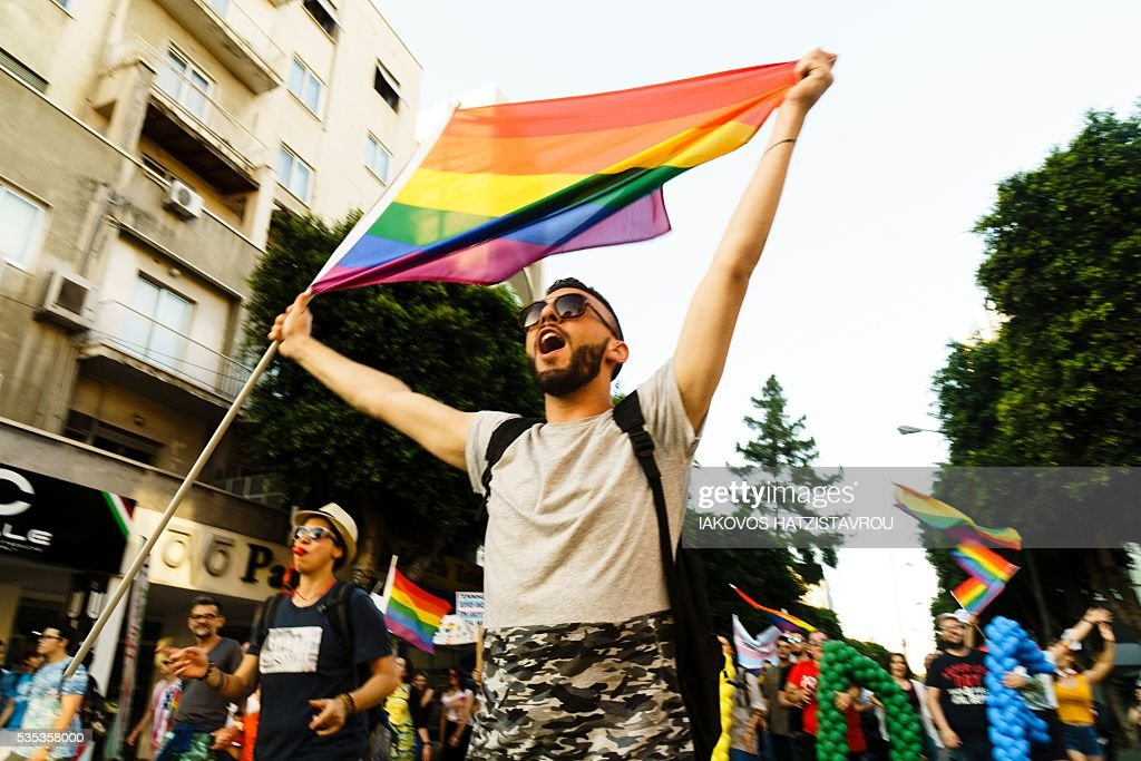 A man waves a rainbow flag, commonly gay pride flag, as he marches during the third edition of the Gay Pride parade on May 29, 2016 in Cyprus' capital Nicosia. / AFP / Iakovos Hatzistavrou