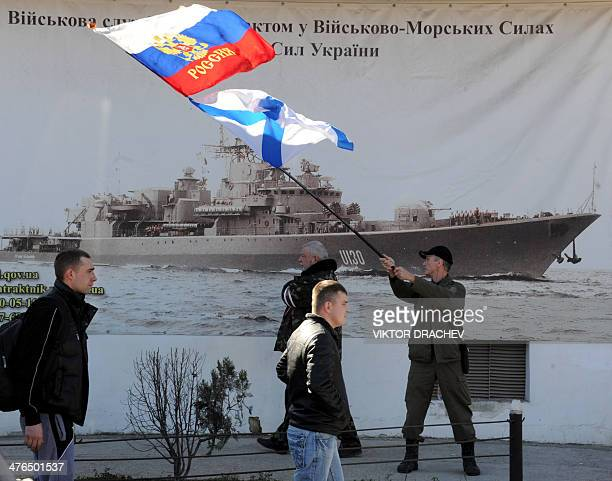 A man waves a Russian flag and a Russian Navy flag in front of the headquarters of the Ukrainian Navy in Sevastopol on March 3 2014 Russian forces...